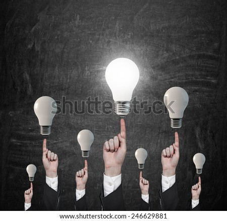 many hands pointing on lightbulbs on gray background