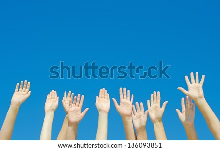 Many hands raised up against the blue sky. - stock photo