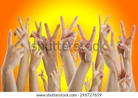 many hands showing victory sign, isolated on sunset - stock photo