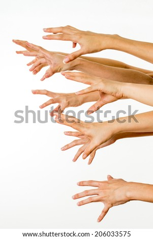 many hands trying to reach or grab something - stock photo