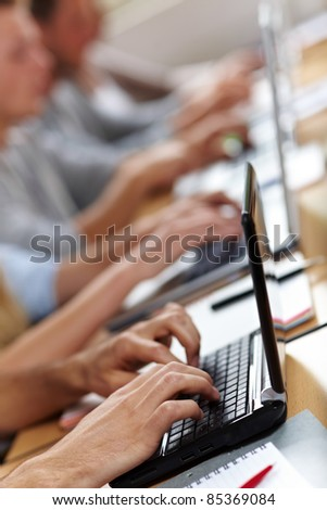 Many hands typing on laptops or netbooks