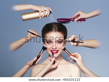 Many hands with cosmetics brush, shadows doing make up of glamour, smiling caucasian girl  - stock photo