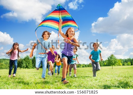 Many happy active kids boys and girls run with kite in the park