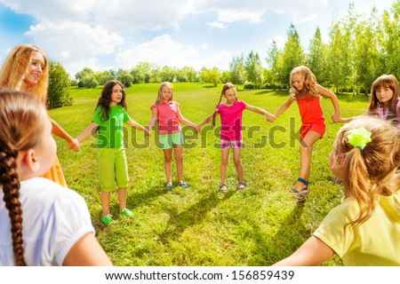 Many happy girls friends play roundelay and stand in circle in the park on the green grass on sunny summer day