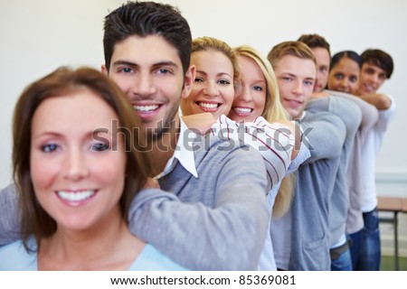 Many happy smiling students leaning on shoulders in a row - stock photo