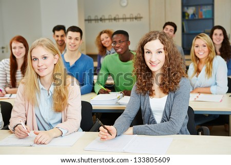 Many happy students sitting in university course classroom - stock photo