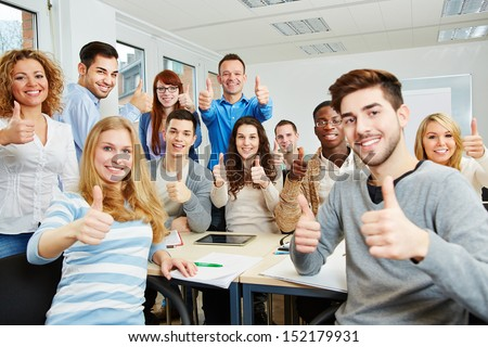Many happy students with teacher holding their thumbs up in university - stock photo