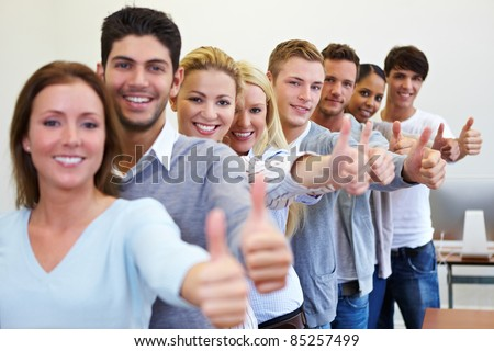 Many happy successful students holding their thumbs up - stock photo