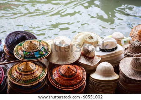 Many hats for sale on Damnoen Saduak Floating Market in Thailand - stock photo