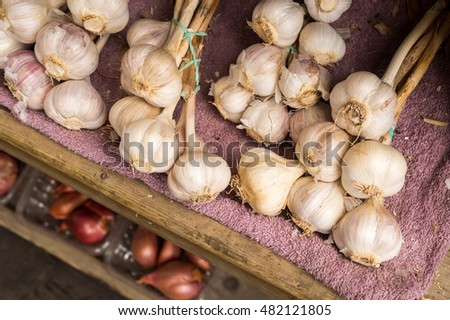 Many heads of garlic drying in a wooden box at the market