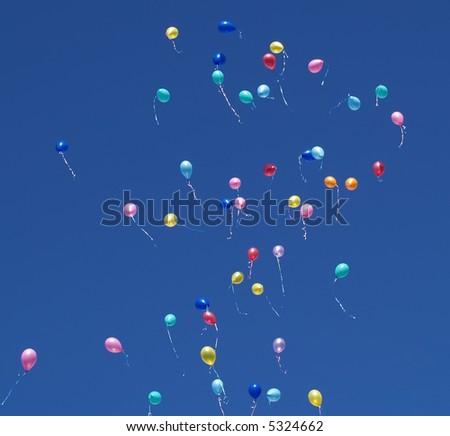 Many helium party balloons floating skyward - stock photo