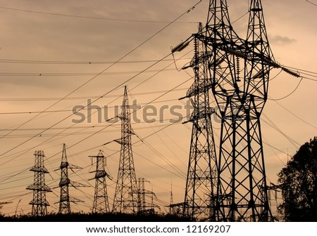 Many high voltage electric lines in the dusk - stock photo