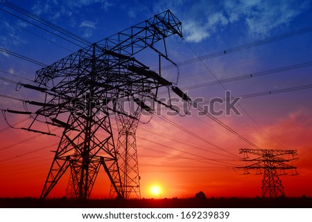 Many high voltage tower under the setting sun exposure in the field   - stock photo