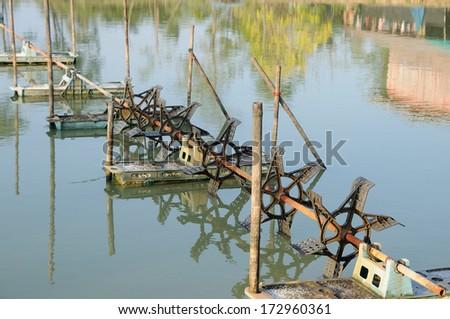 Many Hydraulic turbines in local pond. - stock photo
