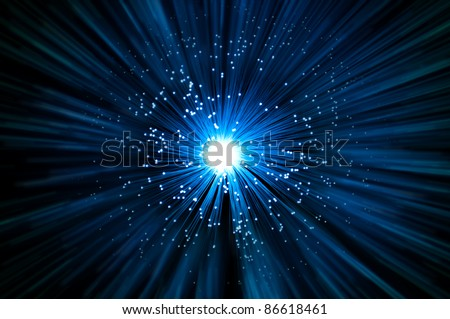 Many illuminated blue fiber optic light strands emitting a blue light effect blur against a dark background. - stock photo