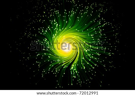 Many illuminated green and yellow fiber optic light strands swirling towards the center against a black background. - stock photo