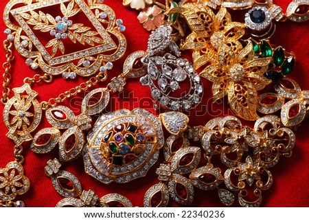 Many jeweleries with colorful gems on red cloth - stock photo