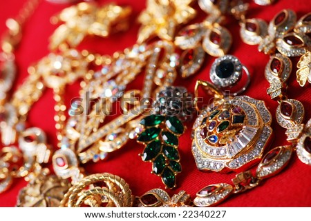 Many jeweleries with colorful gems on red cloth, selective focus on pendant. - stock photo
