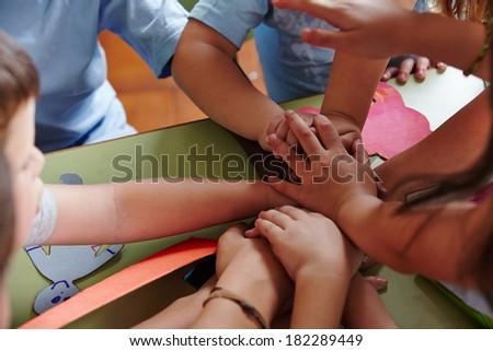 Many kindergarten children stacking their hands in a teamwork effort - stock photo