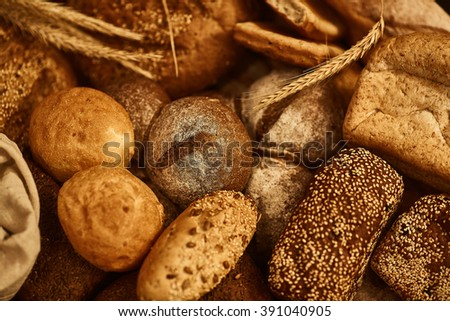 Many kinds of fresh baked bread, wheat ear, dried fruits and cereals on a wooden trellis. White and brown bread, baguette and whole grain bread.