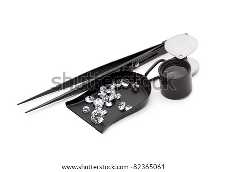Many kinds of jewelers tools - Shovel Bead scoop with loop Handle, magnifier, tweezers and  Diamond with facets that sparkle brightly in the light.