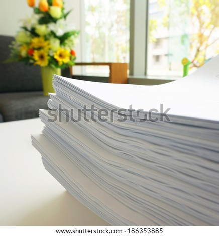 Many large sheets of white papers stacked as a set, placed on desk.                               - stock photo