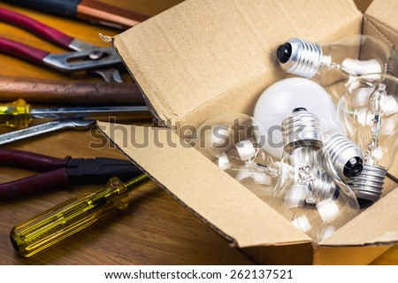 Many light bulbs in cardboard box with tools, change or improve idea concept