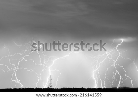 Many lightning bolts striking on the horizon with a cell phone communication tower.    - stock photo