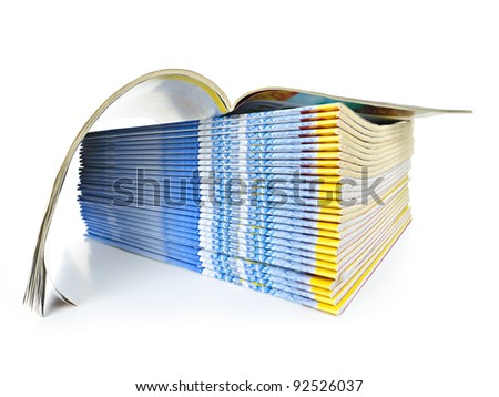 Many magazines stacked in a pile with one open isolated on white - stock photo