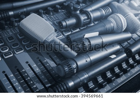 many microphone on audio mixer's in cool tone  - stock photo