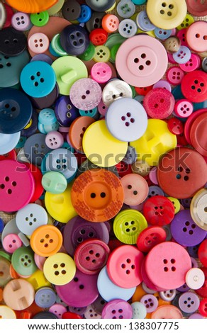 Many mixed, brightly coloured sewing or clothing buttons, filling the frame