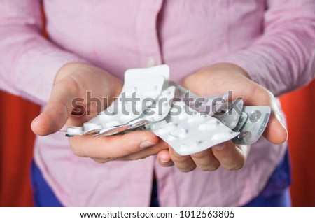 Many multi-colored pills in a Senior's hands on white background Alzheimer's patients caring for the health of the elderly patients