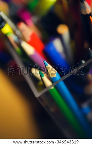 many multicolored pencils in a box. Selective focus on a tip of blue pencil