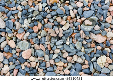 many multicolored wet stones on coast - stock photo