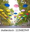 Many multicoloured umbrellas hanging on the street - stock photo