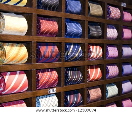 Many neckties displayed on a shelf in a store. Focus is at the two first vertical rows. - stock photo