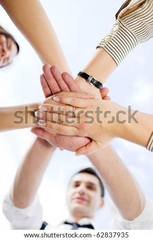 Many office workers holding hands all together across the blue sky demonstrating unity and team work outdoors. - stock photo