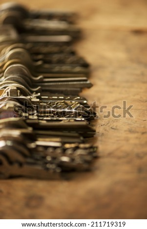 Many old keys, aligned on a well used old wooden desk. Shallow depth of field. - stock photo