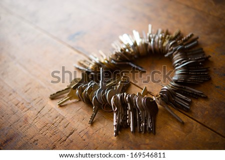 Many old keys on a well used old wooden desk.  - stock photo