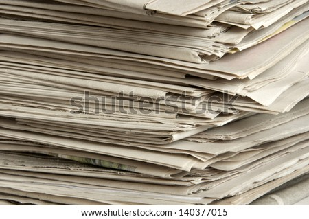 Many old newspapers stacked in a pile.