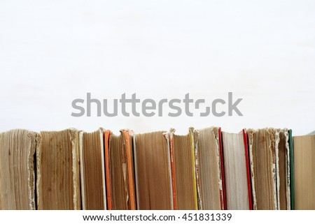 many old shabby books standing in a row on a light surface / used book shelf - stock photo
