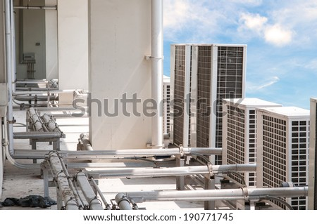 Many older Air compressor on roof with blue sky background. - stock photo