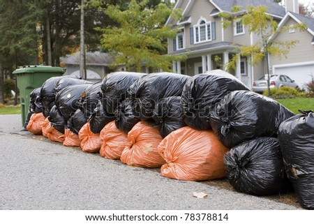 Many orange and green garbage bags at curb - stock photo