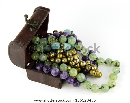 Many ornaments, stone, semi-precious,amethyst,aquamarine, green, blue, and gold-plated metal lay outside the box is full and overflowing antique red wooden on white.  - stock photo