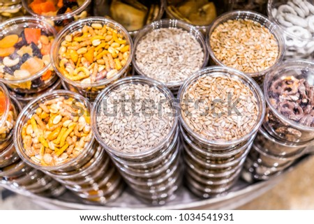 Many packaged seeds, nuts, dried fruit in plastic containers on display on store shop shelves, sunflower seeds mix, pretzels