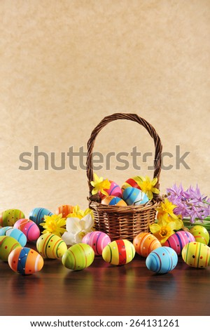 many painted easter eggs with easter nest and hyacinth in front of brown background  - stock photo