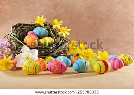 many painted easter eggs with easter nest and narcissus in front of brown background  - stock photo