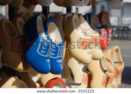 Many pairs of wooden shoes on a dutch market. - stock photo