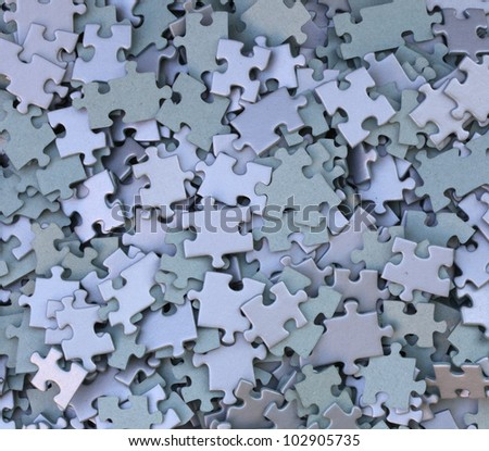 many parts of a disassembled puzzle - stock photo
