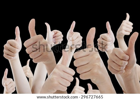 Many people holding their thumbs up on black background - stock photo